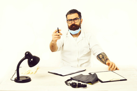 Bearded man, long beard. Brutal caucasian doctor or unshaven hipster in mask, medical gown sitting at table with notebook and stethoscope isolated on white studio background. Medicine concept