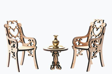 Antique concept, vase on golden tray on decorative wooden table with engraved chairs isolated on white background, copy space