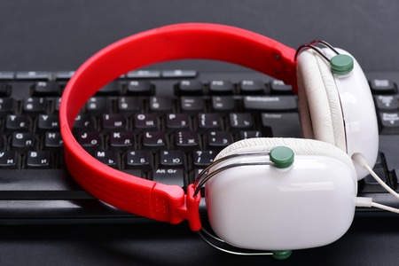 Earphones in red and white colors with computer keyboard. Sound recording and technology idea. Headphones and keyboard. Music and digital equipment concept. Electronic appliances on black background