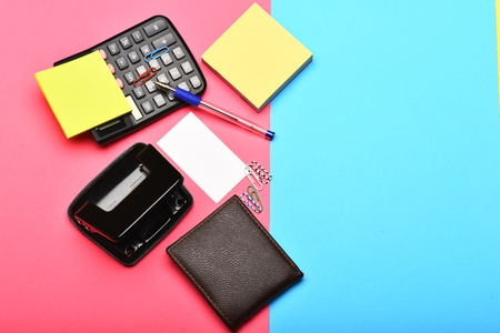 Calculator hole punch business card holder note paper pen office tools isolated on pink and blue background top view calculator hole punch business card note paper pen and clips business and work concept colourmoves