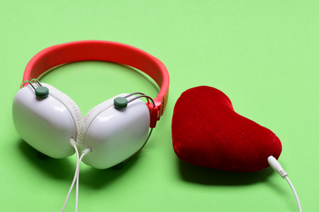 Modern and stylish earphones on light green background. Headset for music and heart shaped player. Headphones in white and red color with soft toy heart. Music accessories and Valentines day concept