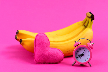 Bunch of bananas next to alarm clock and heart, isolated on magenta pink background. Concept of diet regime and Valentines day Stock Photo