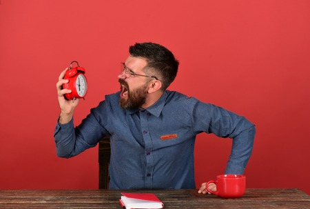 Cup, retro clock and red book on vintage desk. Teacher with beard and glasses holds and yells at alarm clock, red background. Man with angry face sits at wooden table. Exam and studying time concept Stock Photo