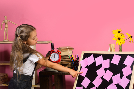 Kid and school supplies on pink background. Childhood and study time concept. Schoolgirl with concentrated face in classroom. Girl holds red alarm clock and points at pink sticky notes on blackboard