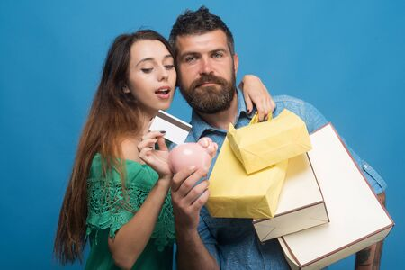 Couple in love with serious and interested faces holding shopping bags on blue background. Bearded man holds pig money box. Guy and lady with credit card do shopping. Shopping and fashion concept Stock Photo