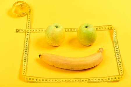 Face with smile made of ripe fruit framed with flexible ruler, isolated on bright yellow background. Concept of weight loss and vitamins