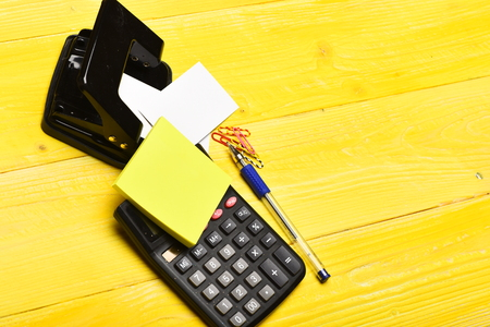 Office tools on yellow table. Calculator, sticky notes, paper clips, hole punch, pen and blank business cards on wooden surface. Stationery on vintage background close up. Business and work concept. Stock Photo