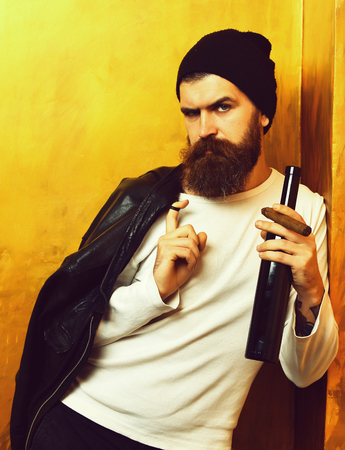 Bearded man, long beard. Brutal caucasian serious unshaven hipster holding bottle and smoking cigar with black leather jacket on shoulder, hat and white shirt on golden studio background Stock Photo