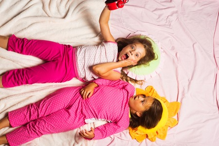 Kids in pink pajamas have fun, put hands up. Children with shocked faces lie on pink background hold alarm clock. Schoolgirls have pajama party with funny pillows. Childhood and oversleeping concept.