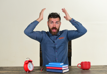 Exam and studying concept. Cup and retro clock with red and blue books on vintage table. Man with beard and glasses on head isolated on white background. Worker with shocked face sits at wooden table Stock Photo