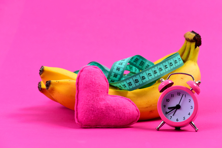 Composition of alarm clock, heart and greenish blue measuring tape on bananas, isolated on raspberry pink background
