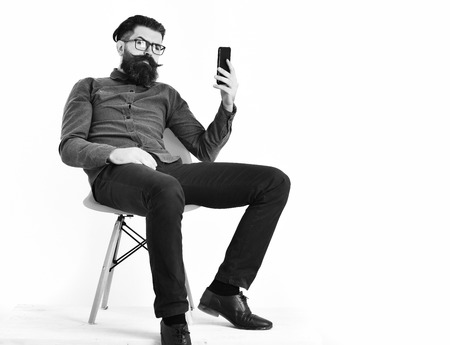 Bearded man, long beard. Brutal caucasian unshaven serious hipster with glasses and moustache making selfie on cell phone, sitting on orange chair, wearing blue shirt isolated on white background