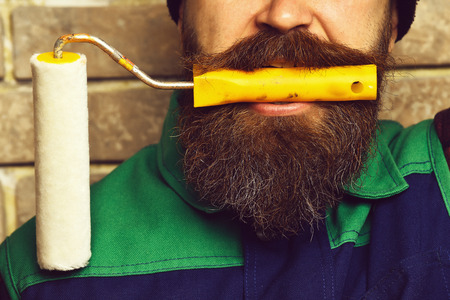 hair roller: bearded painter man, long beard, brutal caucasian hipster with moustache in black cap holding in his mouth roller paint with serious face on brick wall studio background, closeup Stock Photo
