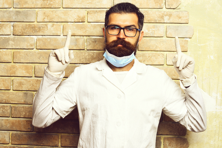 Bearded man, long beard. Brutal caucasian doctor or unshaven hipster, postgraduate student in medical gown, glasses and gloves on beige brick wall studio background. Medicine concept