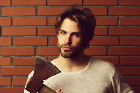 Bearded guy with suspicious look and cunning face expression holds old axe, red brick wall background