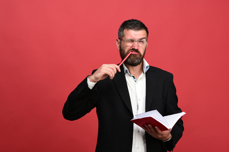 Man with funny face holds book and pencil in mouth, on red background
