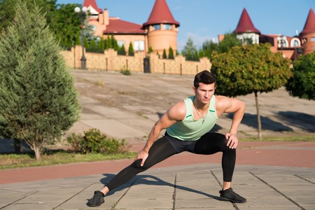 Man stretching and warming up muscles before workout. Athlete training on sunny summer day outdoors. Fit macho in track suit on urban landscape. Sport and fitness. Healthy lifestyle concept.