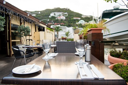 dining table and chairs: Restaurant terrace with tables, chairs and yacht in sea in Philipsburg, Sint Maarten. Glasses and cutlery. Eating and dining outdoors. Summer vacation and holidays. Eat, drink, enjoy concept. Stock Photo
