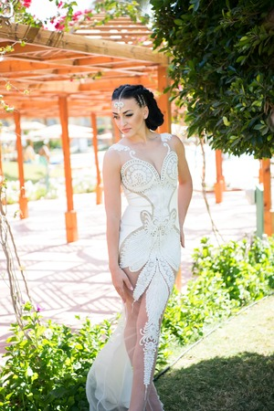 Girl in sexy white dress on sunny summer day. Bride in white wedding dress. Woman with jewelry tiara in brunette hair. Beauty and fashion concept.
