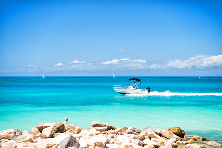 맑은 날에 푸른 하늘에 푸른 바다 물 위에 빠르게 떠있는 모터 보트. 여름 휴가 및 여행 개념입니다. 스톡 콘텐츠