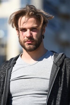 Man with bearded face and blond hair haircut in grey tshirt standing on sunny day outdoors. Fashion, beauty, skincare, hairdressing, barber salon concept. Stock Photo
