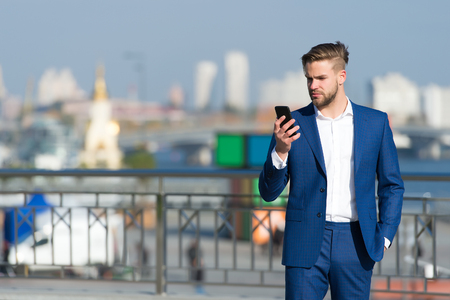 Man in formal outfit with mobile phone. Businessman or ceo urban fashion. Manager with beard on serious face hold phone. Business communication and digital marketing. modern life and new technology.