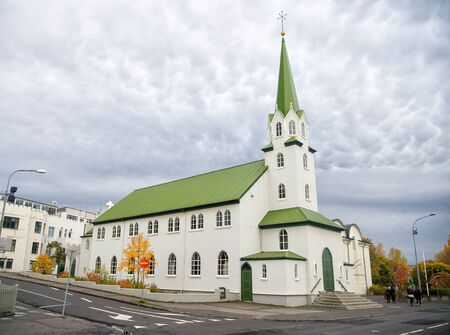 Church building with white walls and green roof on cloudy sky in Reykjavik, Iceland. Architecture, landmark, worship service, religion, faith concept