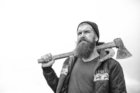 Lumberjack brutal bearded man with axe on shoulder on sky background. Logging and chopping concept, black and white
