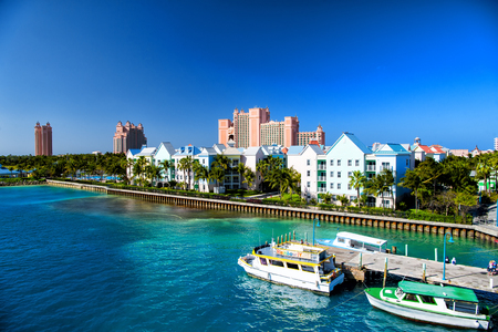 Resort hotel building villa with green palm tree tropic garden on sea beach on sunny day on blue sky in Nassau, Bahamas. Summer vacation, recreation, lifestyle, traveling concept, Hotel atlantis