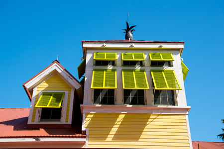 House with open yellow window shutters with pineapple on terracotta roof on sunny day on blue sky in Nassau, Bahamas. Architecture, structure, design. Summer vacation concept, Hotel atlantis