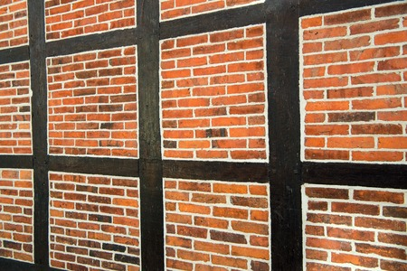 Architecture, construction and building concept. House wall of red bricks and wood textured surface on brickwork background.