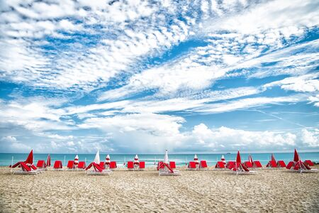 South beach, miami. sea beach with sunbeds and umbrellas on natural background in Miami, USA. Summer vacation in paradise. Sunbathing and swimming concept. Recreation, relax and lounge Stock Photo