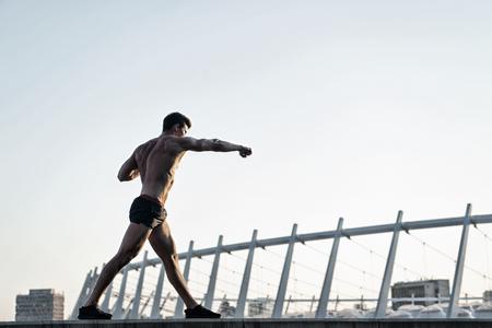 Hombre haciendo ejercicios de boxeo en el techo. Fitness y deporte Atleta entrenando al aire libre. Concepto de estilo de vida saludable. Deportista con cuerpo musculoso en el cielo blanco.