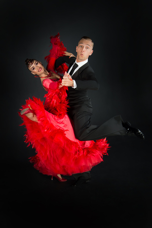 dance ballroom couple in red dress dance pose isolated on black background. sensual professional dancers dancing walz, tango, slowfox and quickstep.