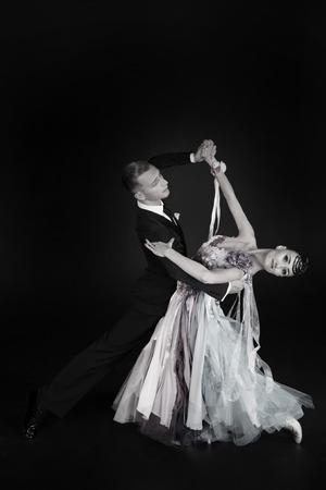 dans ballroom paar in jurk dans vormen geïsoleerd op zwarte achtergrond. sensuele professionele dansers dansen walz, tango, slowfox en quickstep. zwart en wit
