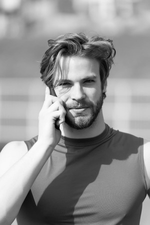 happy fashion model with mobile or cell phone. athletic bearded man or sexy handsome guy, muscular body sunny outdoor in blue sportswear. summer activity and sport. healthy lifestyle and communication