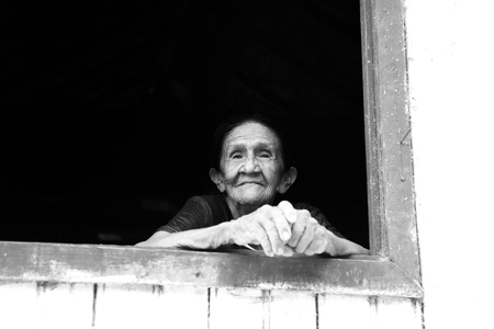 Boca de Valeria, Brazil - December 03, 2015: old mature mulatto woman with kind smiling face holding hands together standing in wooden window brown and white color looking outdoor Editorial
