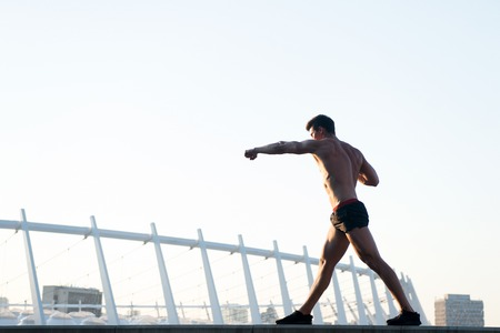 Sportsman with muscular body on white sky. Athlete training outdoors. Healthy lifestyle concept. Fitness and sport. Man doing boxing exercises on roof.