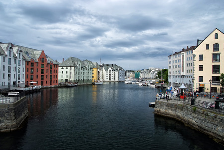 Alesund, Norway - January 16, 2010: water canal with houses and port in town on cloudy sky background. Vacation, traveling, wanderlust concept