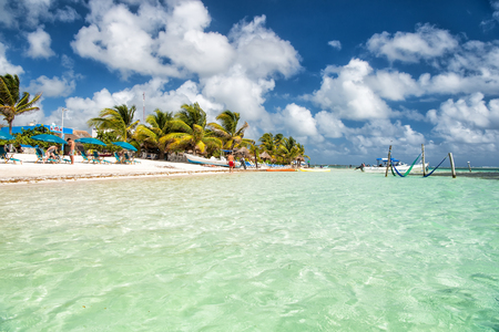 Summer vacation, travelling concept. Sea or ocean beach with green palm trees, umbrellas on sand at Costa Maya, Mexico. Tropical resort on sunny day on cloudy blue sky.