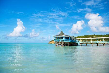 セントジョンズ、アンティグアに青い空を背景に晴れた日の熱帯のビーチに青緑色の海や大洋の水で木造の待合い所と桟橋。夏の休暇の概念