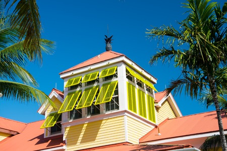 Mansard with open yellow window shutters and pineapple on terracotta roof on sunny day on blue sky in Nassau, Bahamas. Architecture, building, structure, design. Summer vacation concept, Hotel atlantis