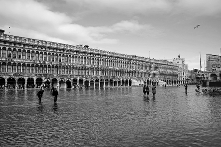 Venice, Italy - May 16, 2008: tourists and beautiful old buildings, palaces, sights, at city square under high water or tide on blue sky background