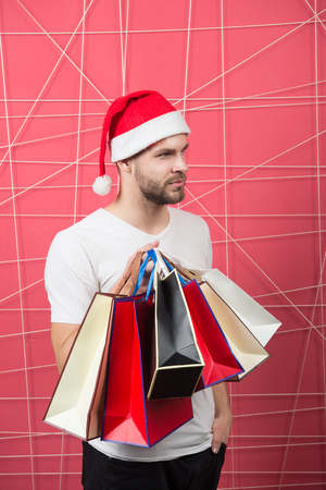 Winter holidays celebration. Man santa with shopping bags on pink background. Christmas, new year gift, present. xmas sale concept. Macho shopper in red hat hold paperbags. Stock Photo