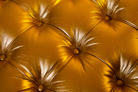 Leather texture padded with buttons on golden background. Furniture, upholstery, decoration, design concept. Stock Photo