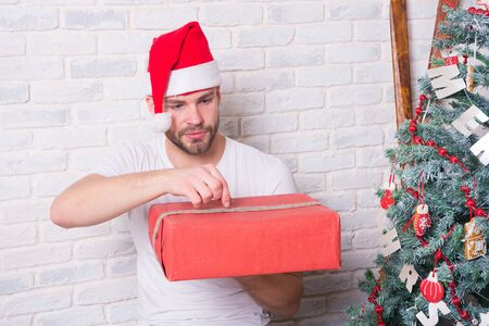 Holidays preparation and celebration. Gift giving and exchange. Man santa with box at christmas tree. Macho in red hat hold wrapped present. Boxing day concept.