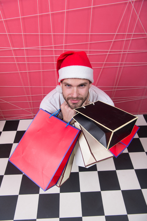 Shopper in red hat with paperbags, top view. Man santa hold bags on black and white checkered floor. Christmas, new year presents. Winter sale, shopping concept. Holidays preparation and celebration.
