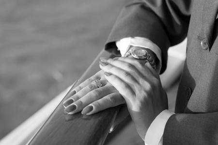 Mani femminili e orologio da polso con il manicure rosso e anello d'oro al dito con diamanti in prossimità di acqua Archivio Fotografico - 90682602