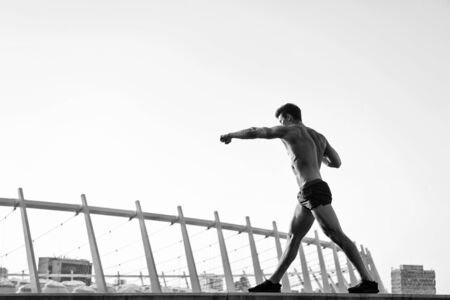 Healthy lifestyle concept. Athlete training outdoors. Sportsman with muscular body on clear sky. Fitness and sport. Man doing boxing exercises on roof, black and white Stock Photo