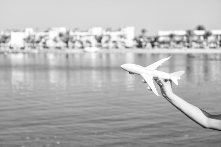 takeoff of white toy plane in female hand on sunny blurred natural background with water. business traveling and vacation. freedom and inspiration. airmail and postal delivery concept, copy space Stock Photo